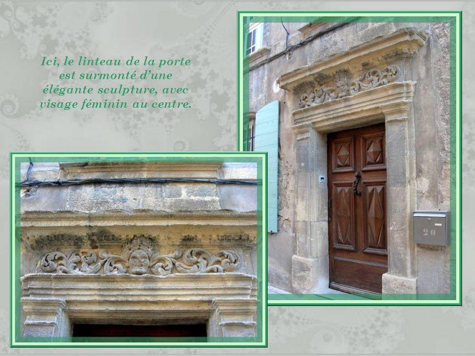 Ici, le linteau de la porte est surmonté d'une élégante sculpture, avec visage féminin au centre.