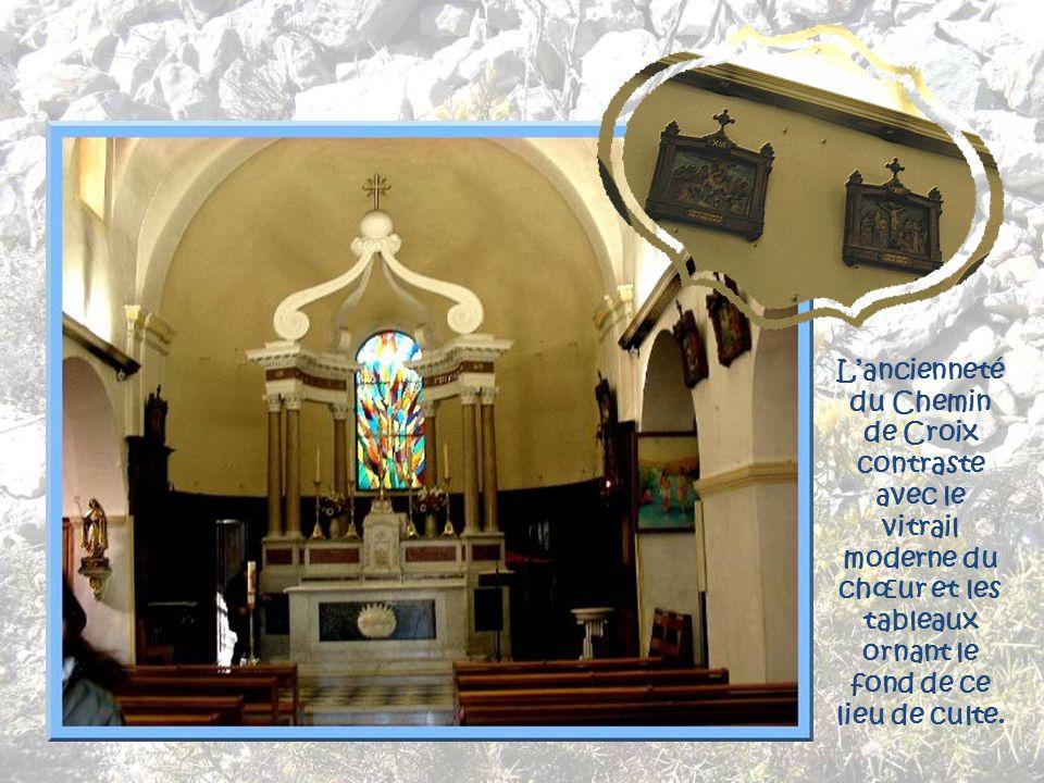 L'ancienneté du Chemin de Croix contraste avec le vitrail moderne du chœur et les tableaux ornant le fond de ce lieu de culte.