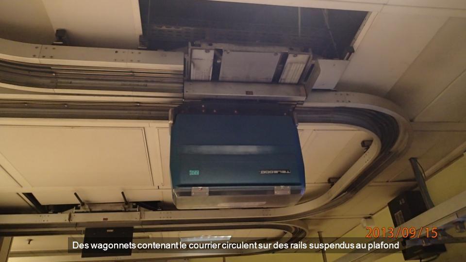 Des wagonnets contenant le courrier circulent sur des rails suspendus au plafond