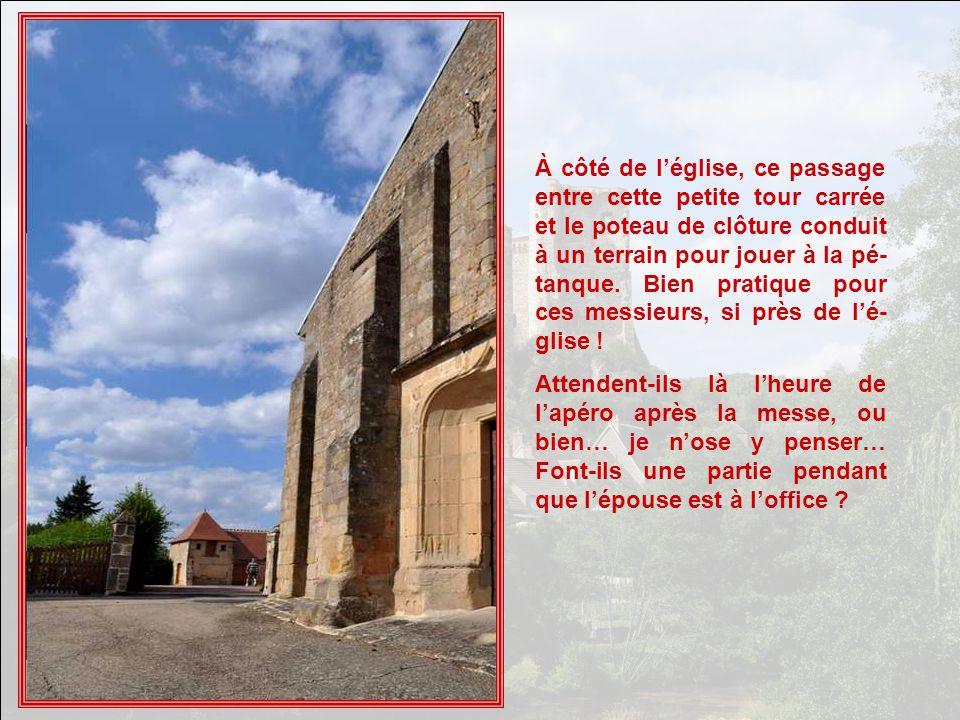 À côté de l'église, ce passage entre cette petite tour carrée et le poteau de clôture conduit à un terrain pour jouer à la pé-tanque. Bien pratique pour ces messieurs, si près de l'é-glise !