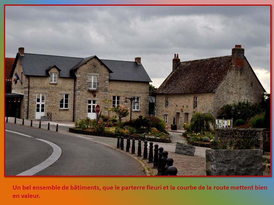 Un bel ensemble de bâtiments, que le parterre fleuri et la courbe de la route mettent bien en valeur.