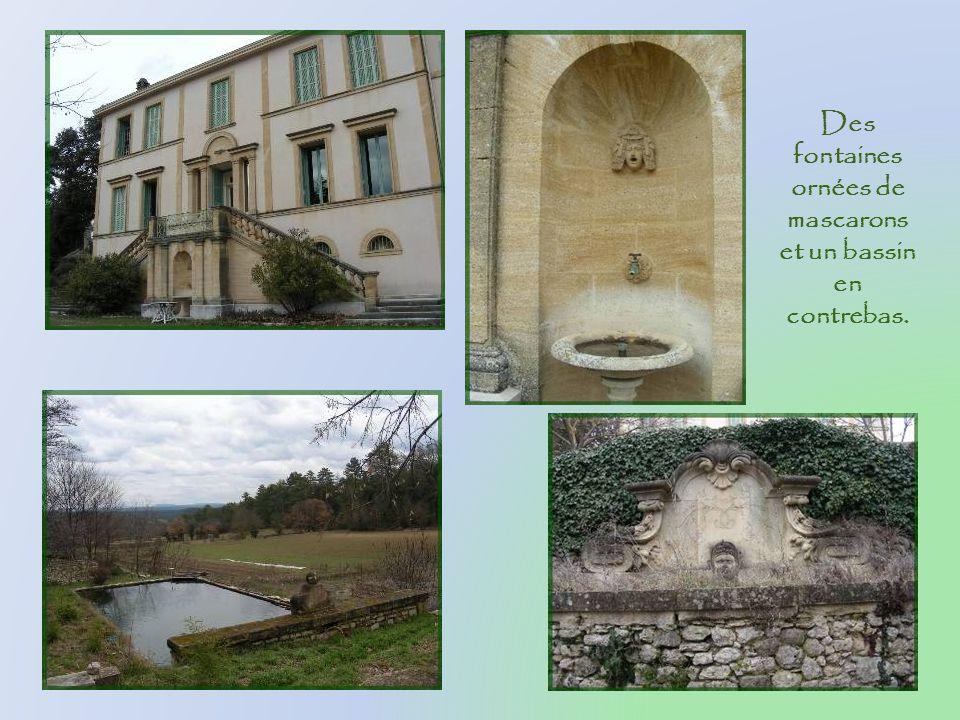 Des fontaines ornées de mascarons et un bassin en contrebas.