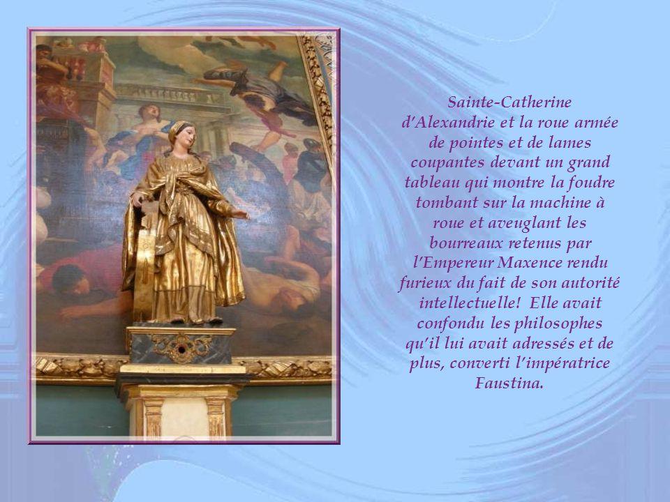 Sainte-Catherine d'Alexandrie et la roue armée de pointes et de lames coupantes devant un grand tableau qui montre la foudre tombant sur la machine à roue et aveuglant les bourreaux retenus par l'Empereur Maxence rendu furieux du fait de son autorité intellectuelle.