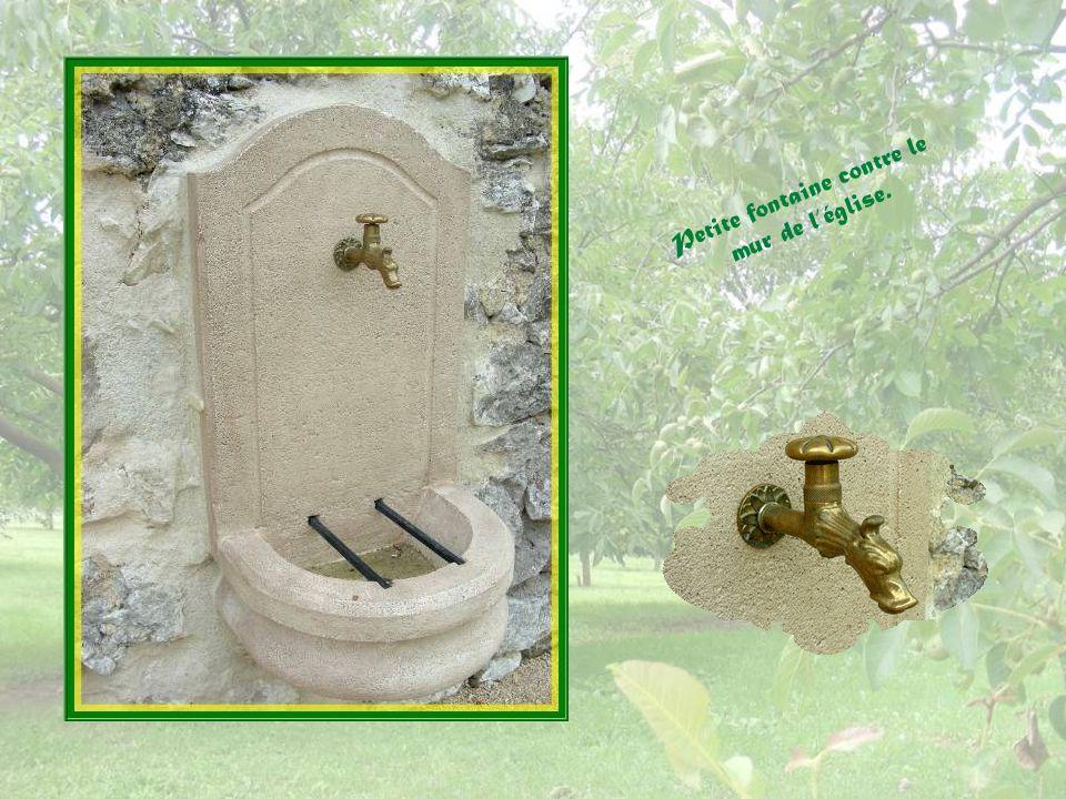 Petite fontaine contre le mur de l'église.