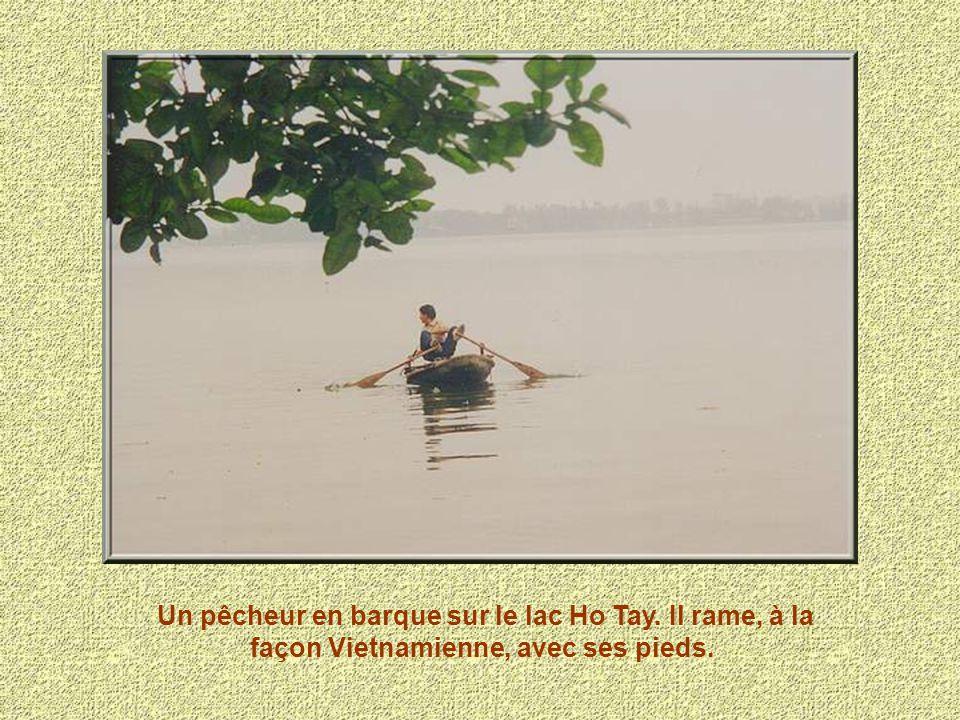 Un pêcheur en barque sur le lac Ho Tay
