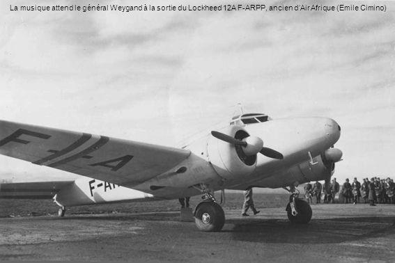 La musique attend le général Weygand à la sortie du Lockheed 12A F-ARPP, ancien d'Air Afrique (Emile Cimino)