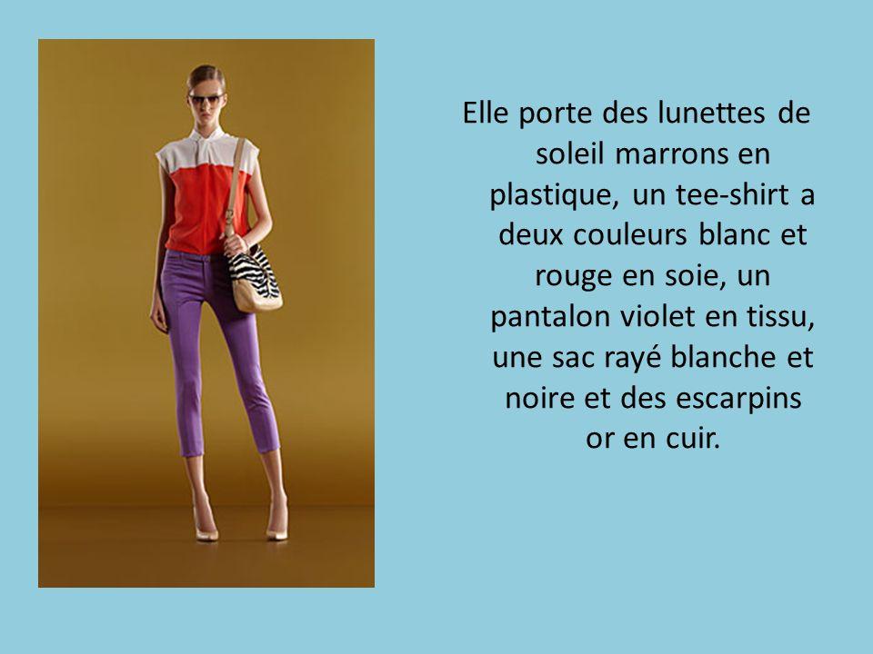 Elle porte des lunettes de soleil marrons en plastique, un tee-shirt a deux couleurs blanc et rouge en soie, un pantalon violet en tissu, une sac rayé blanche et noire et des escarpins or en cuir.