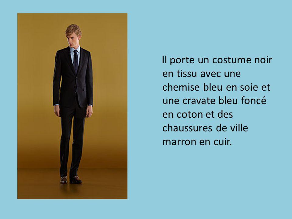 Il porte un costume noir en tissu avec une chemise bleu en soie et une cravate bleu foncé en coton et des chaussures de ville marron en cuir.