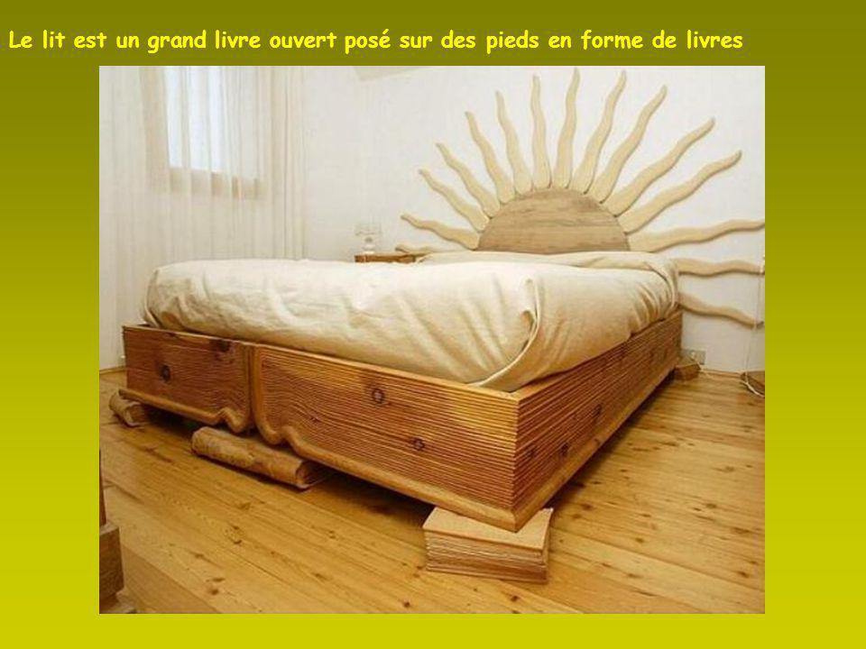 Le lit est un grand livre ouvert posé sur des pieds en forme de livres