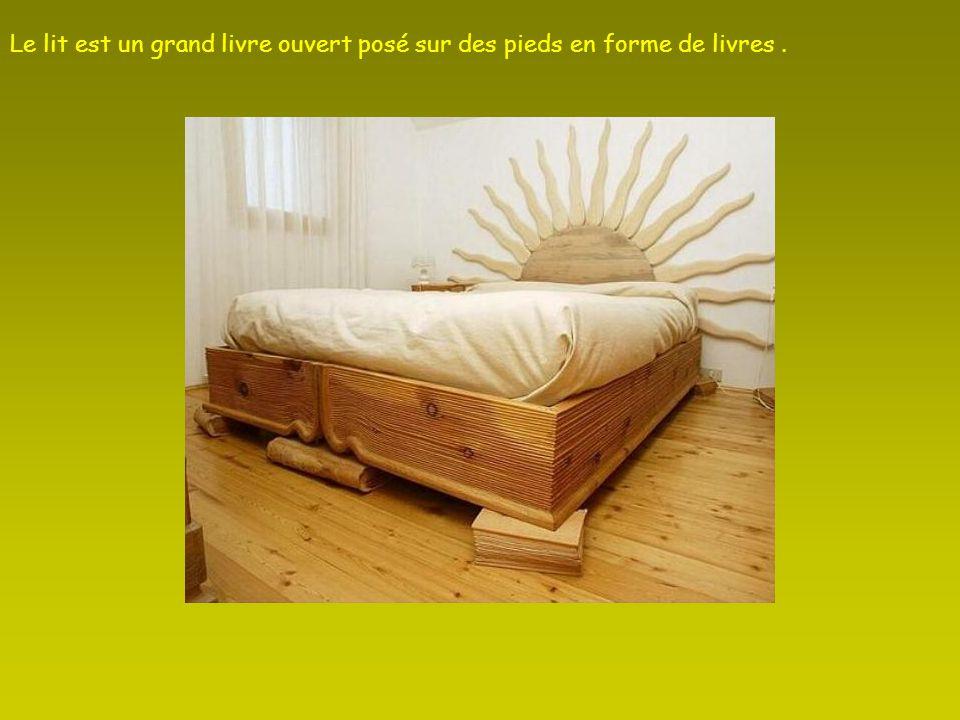 Le lit est un grand livre ouvert posé sur des pieds en forme de livres .