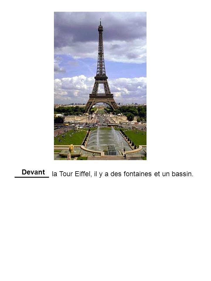 Devant _________ la Tour Eiffel, il y a des fontaines et un bassin.
