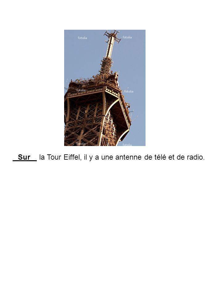 ______ la Tour Eiffel, il y a une antenne de télé et de radio.