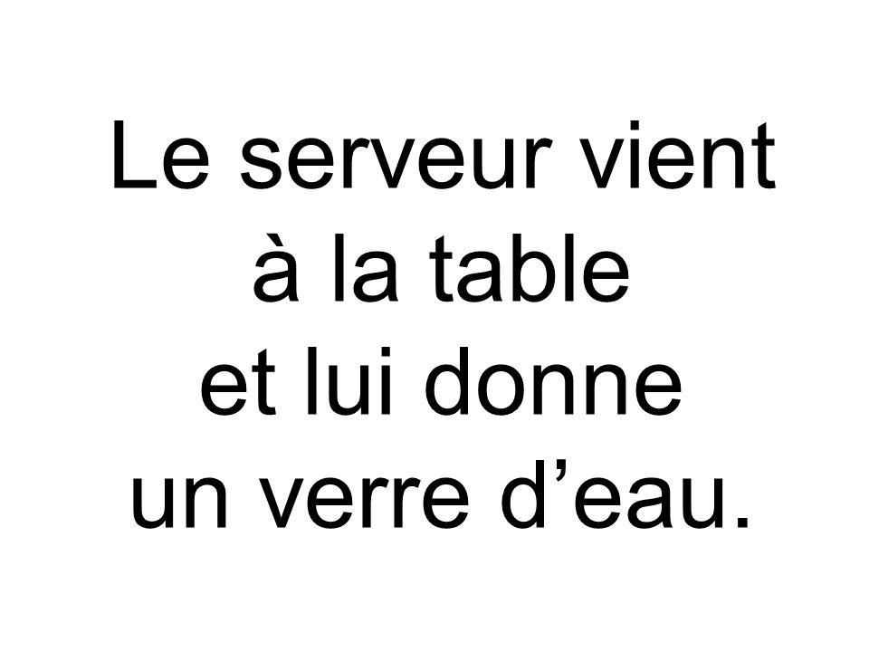 Le serveur vient à la table et lui donne un verre d'eau.