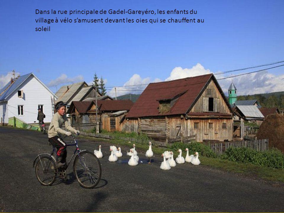 Dans la rue principale de Gadel-Gareyéro, les enfants du village à vélo s'amusent devant les oies qui se chauffent au soleil