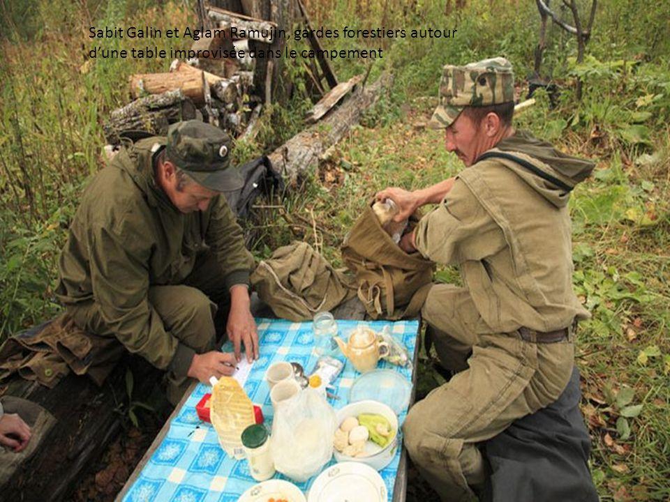 Sabit Galin et Aglam Ramujin, gardes forestiers autour d'une table improvisée dans le campement