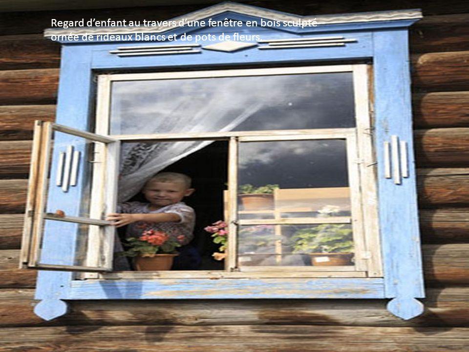 Regard d'enfant au travers d'une fenêtre en bois sculpté ornée de rideaux blancs et de pots de fleurs.