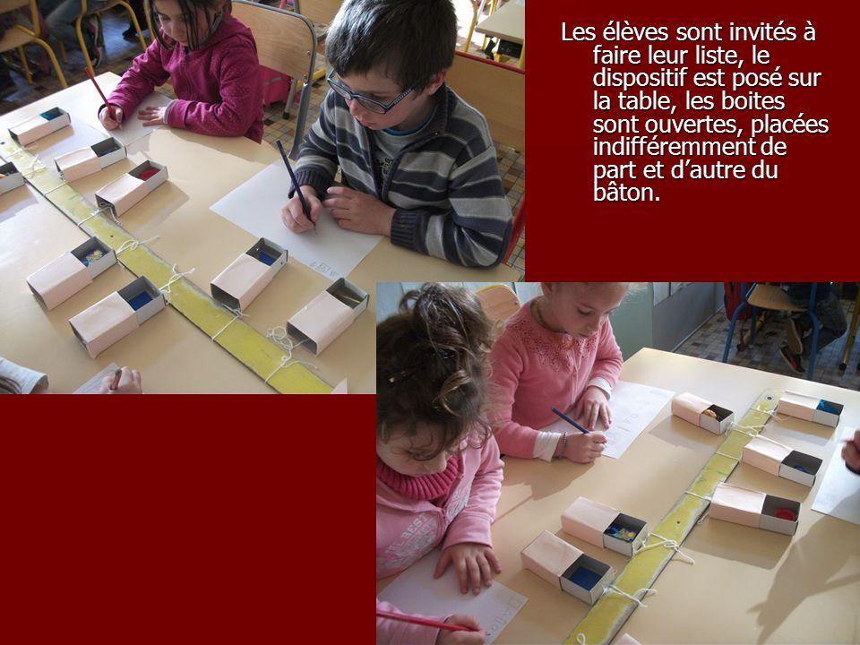 Les élèves sont invités à faire leur liste, le dispositif est posé sur la table, les boites sont ouvertes, placées indifféremment de part et d'autre du bâton.