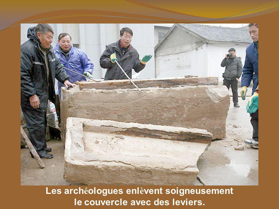 Les archéologues enlèvent soigneusement le couvercle avec des leviers.