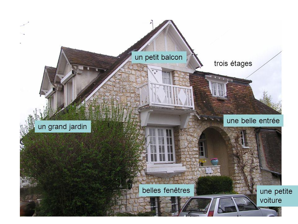 un petit balcon trois étages une belle entrée un grand jardin belles fenêtres une petite voiture