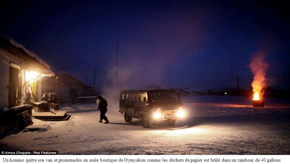 Un homme quitte son van et promenades en seule boutique de Oymyakon comme les déchets de papier est brûlé dans un tambour de 40 gallons