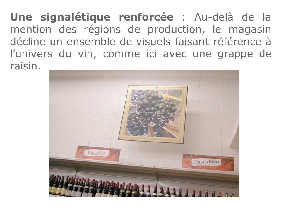 Une signalétique renforcée : Au-delà de la mention des régions de production, le magasin décline un ensemble de visuels faisant référence à l'univers du vin, comme ici avec une grappe de raisin.