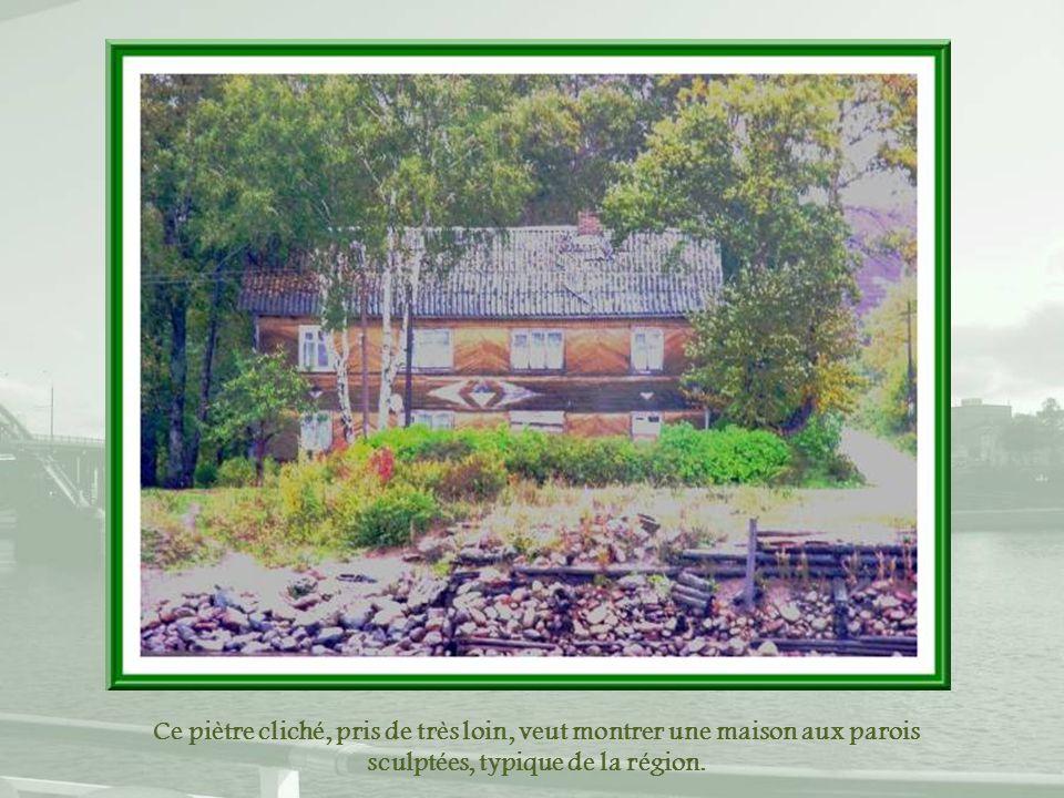 Ce piètre cliché, pris de très loin, veut montrer une maison aux parois sculptées, typique de la région.