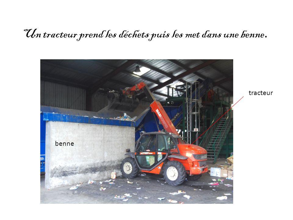 Un tracteur prend les déchets puis les met dans une benne.