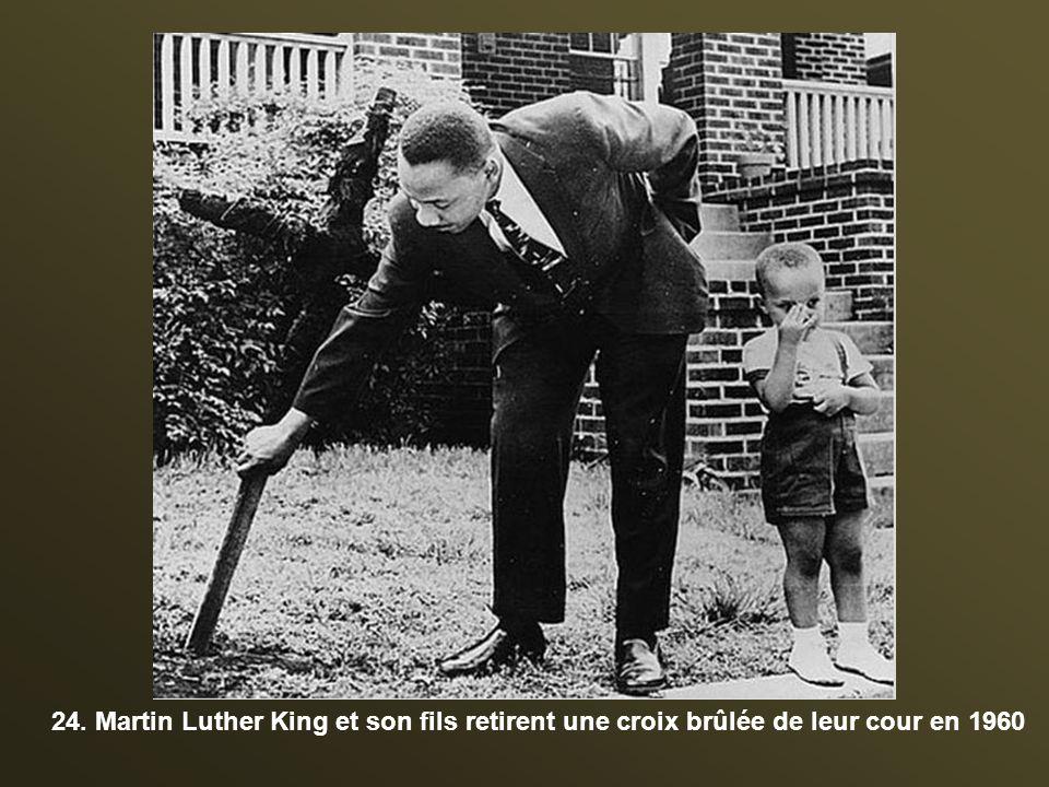 24. Martin Luther King et son fils retirent une croix brûlée de leur cour en 1960