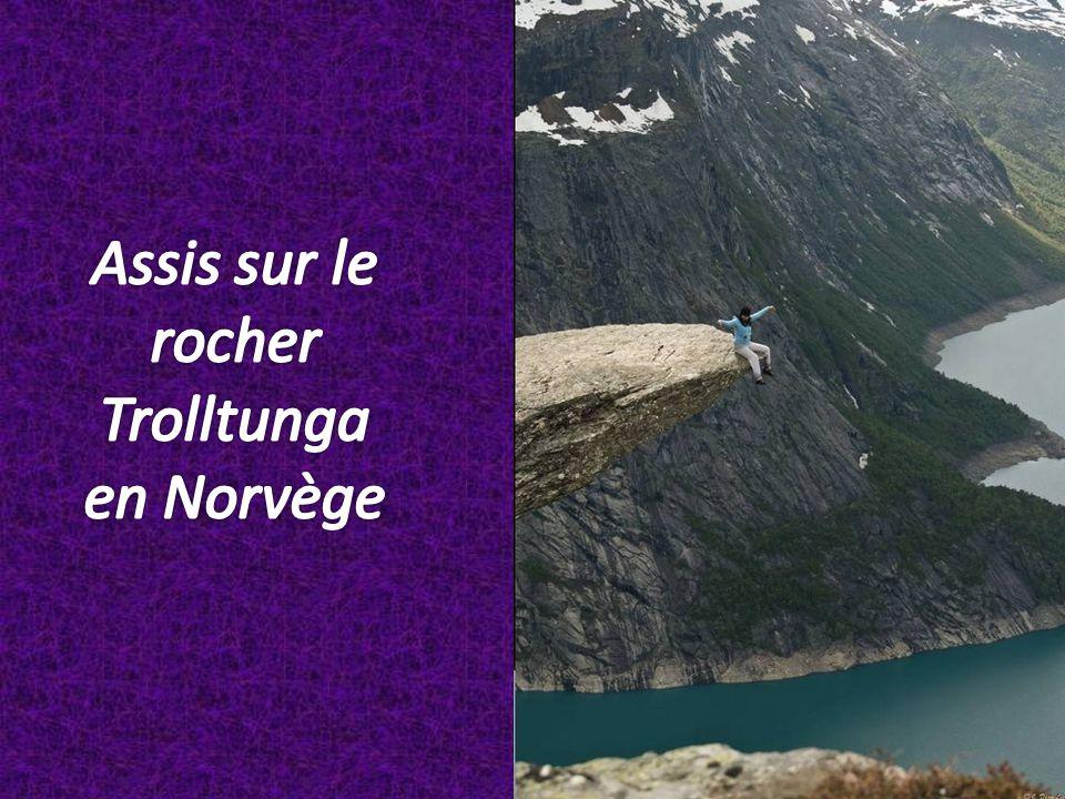 Assis sur le rocher Trolltunga en Norvège