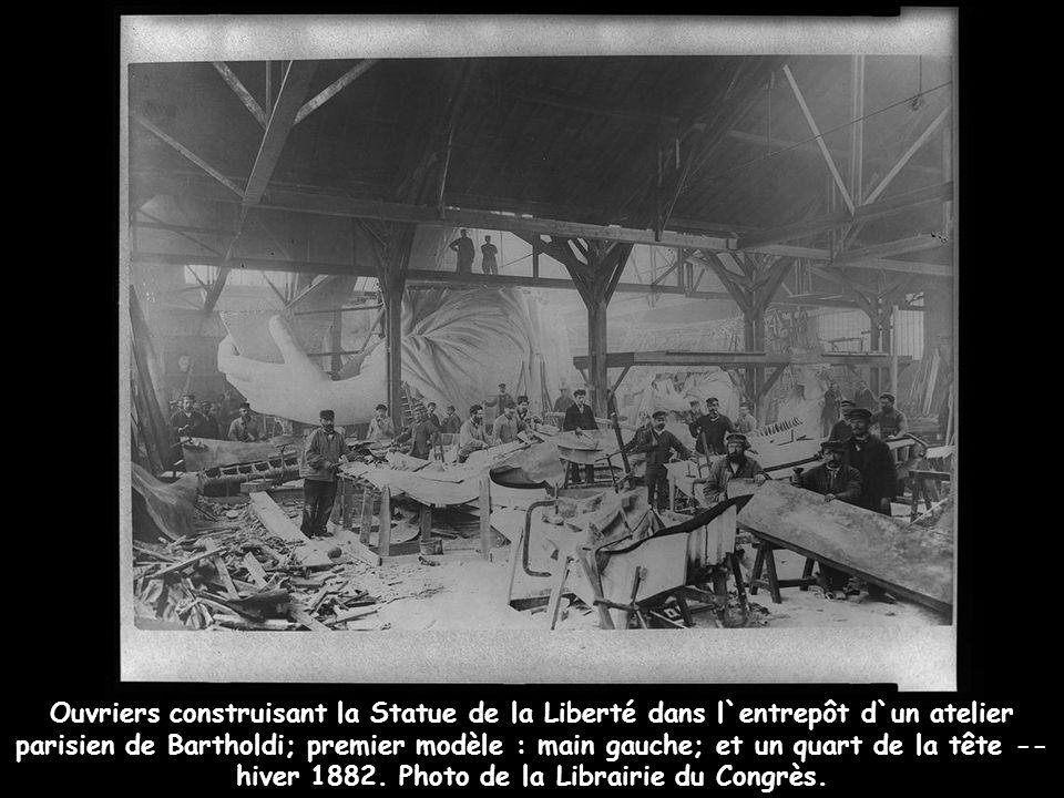 Ouvriers construisant la Statue de la Liberté dans l`entrepôt d`un atelier parisien de Bartholdi; premier modèle : main gauche; et un quart de la tête -- hiver 1882.