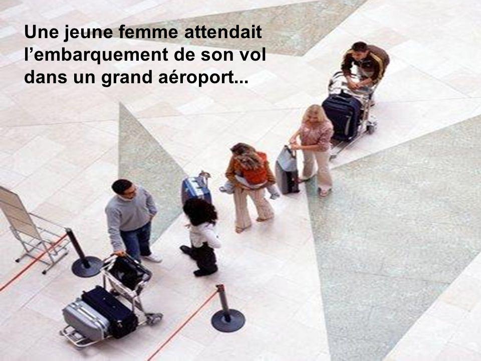 Une jeune femme attendait l'embarquement de son vol dans un grand aéroport...