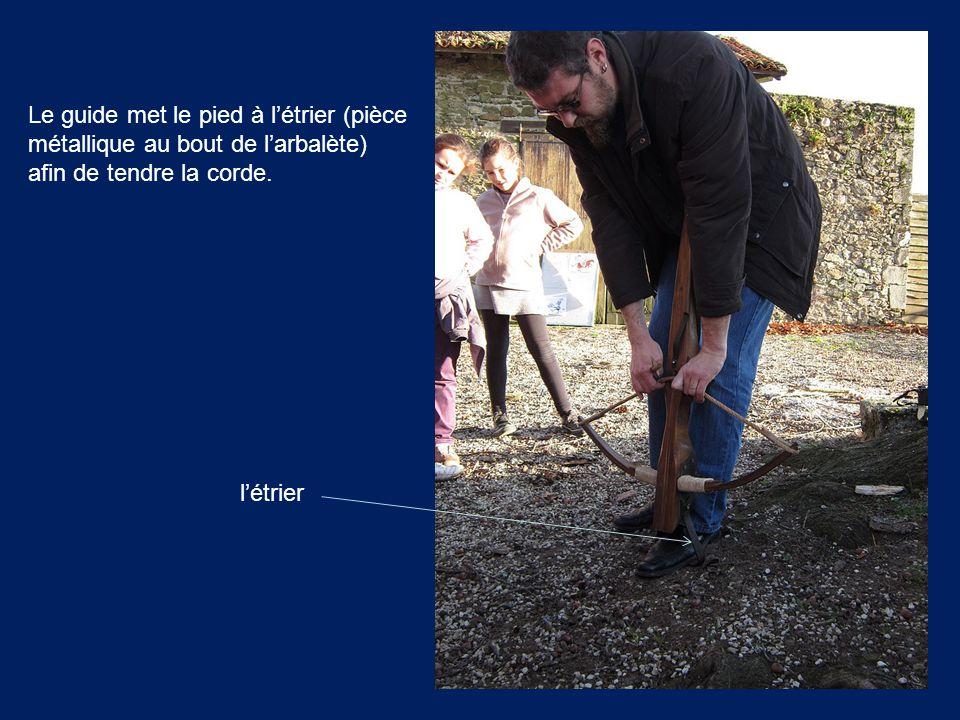 Le guide met le pied à l'étrier (pièce métallique au bout de l'arbalète) afin de tendre la corde.
