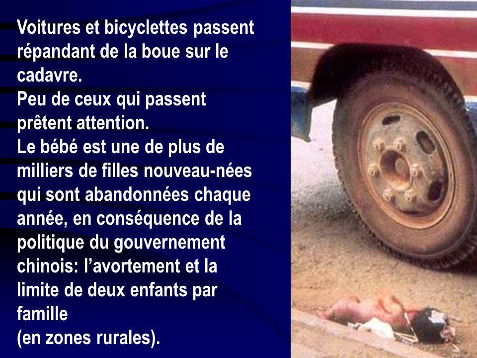 Voitures et bicyclettes passent répandant de la boue sur le cadavre.