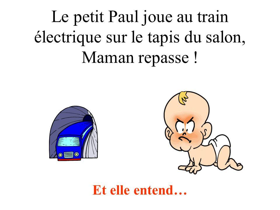Le petit Paul joue au train électrique sur le tapis du salon, Maman repasse !