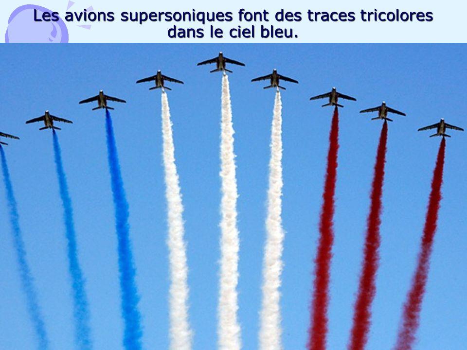 Les avions supersoniques font des traces tricolores dans le ciel bleu.