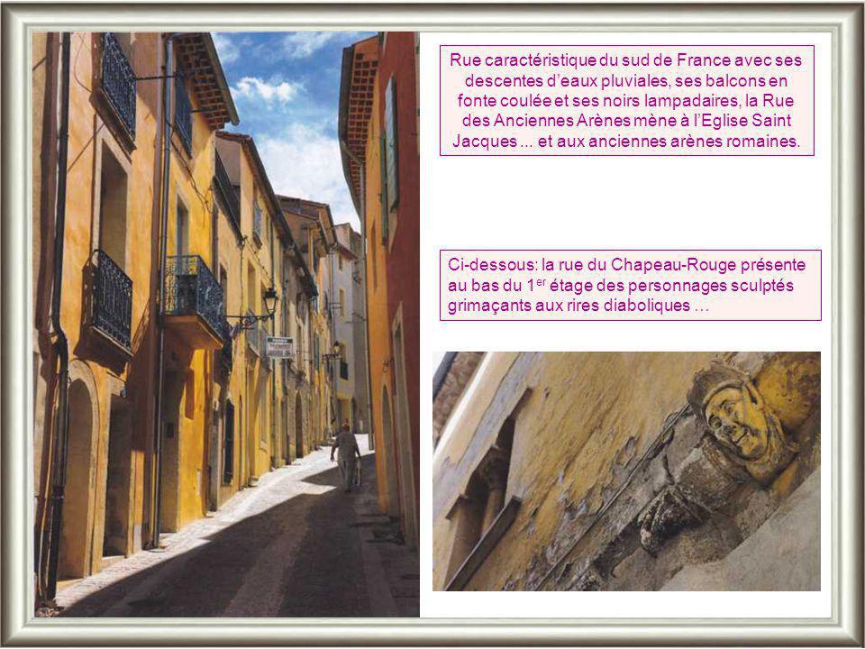 Rue caractéristique du sud de France avec ses descentes d'eaux pluviales, ses balcons en fonte coulée et ses noirs lampadaires, la Rue des Anciennes Arènes mène à l'Eglise Saint Jacques ... et aux anciennes arènes romaines.