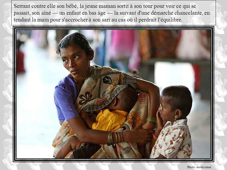 Serrant contre elle son bébé, la jeune maman sortit à son tour pour voir ce qui se passait, son aîné — un enfant en bas âge — la suivant d une démarche chancelante, en tendant la main pour s accrocher à son sari au cas où il perdrait l équilibre.