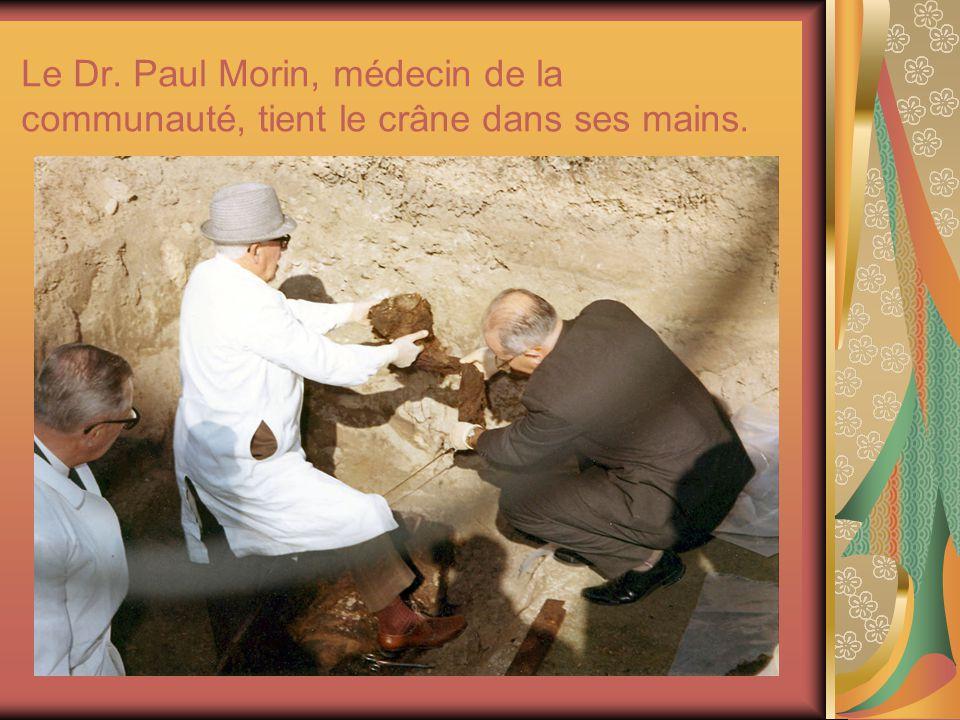Le Dr. Paul Morin, médecin de la communauté, tient le crâne dans ses mains.