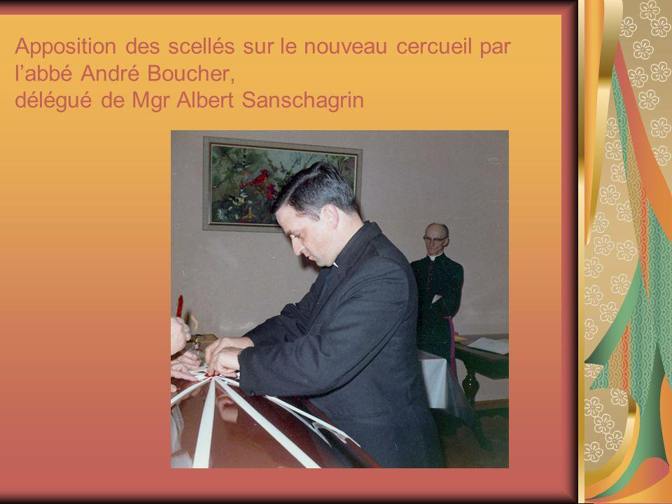 Apposition des scellés sur le nouveau cercueil par l'abbé André Boucher, délégué de Mgr Albert Sanschagrin