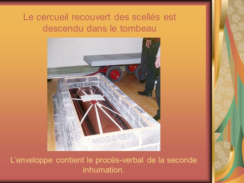 Le cercueil recouvert des scellés est descendu dans le tombeau