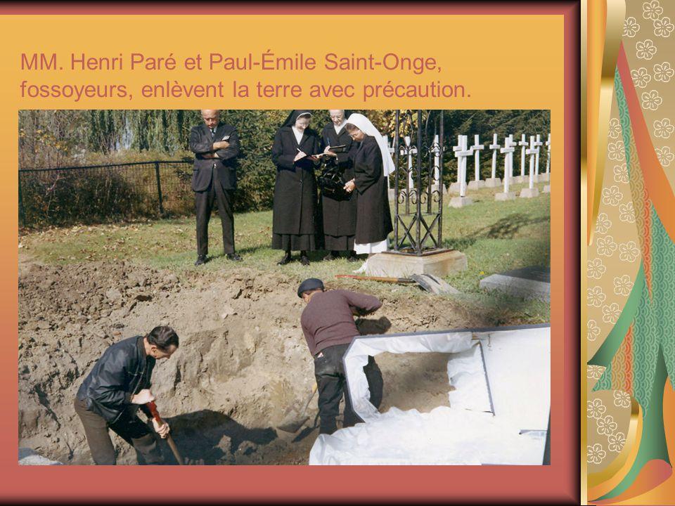 MM. Henri Paré et Paul-Émile Saint-Onge, fossoyeurs, enlèvent la terre avec précaution.