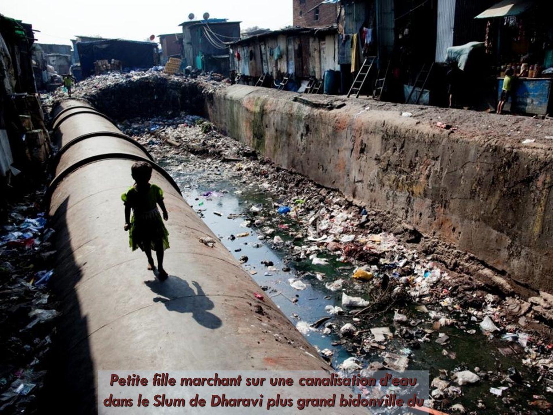 Petite fille marchant sur une canalisation d'eau dans le Slum de Dharavi plus grand bidonville du monde