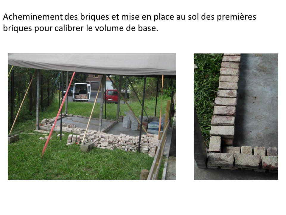 Acheminement des briques et mise en place au sol des premières briques pour calibrer le volume de base.