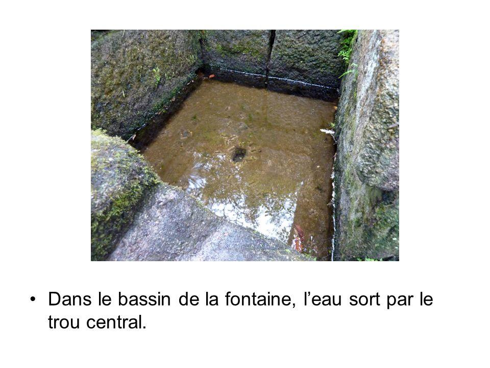 Dans le bassin de la fontaine, l'eau sort par le trou central.