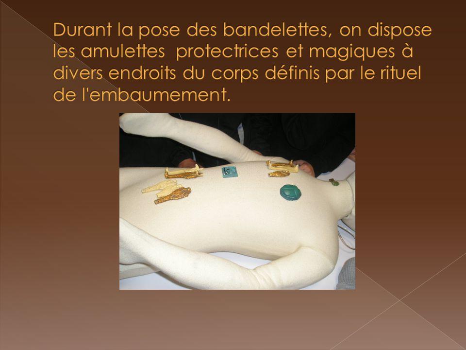 Durant la pose des bandelettes, on dispose les amulettes protectrices et magiques à divers endroits du corps définis par le rituel de l embaumement.