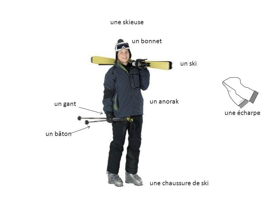 une skieuse un bonnet un ski un anorak un gant une écharpe un bâton une chaussure de ski