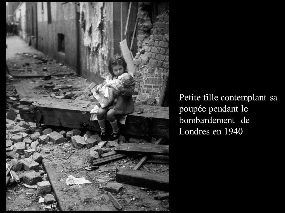 Petite fille contemplant sa poupée pendant le bombardement de Londres en 1940