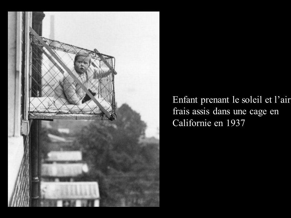 Enfant prenant le soleil et l'air frais assis dans une cage en Californie en 1937