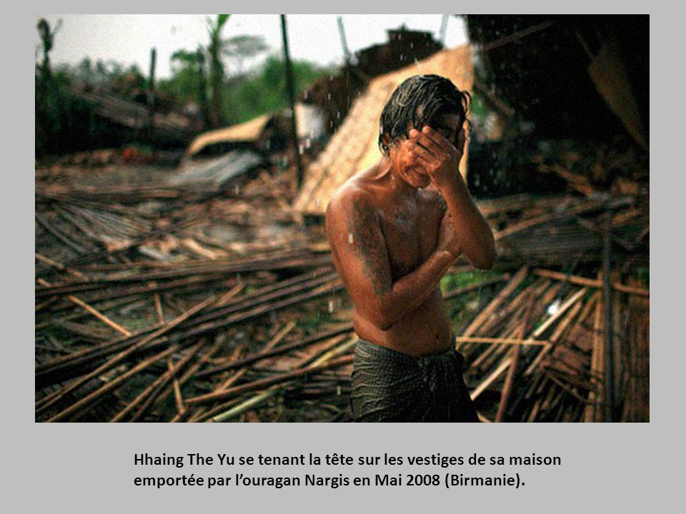 Hhaing The Yu se tenant la tête sur les vestiges de sa maison emportée par l'ouragan Nargis en Mai 2008 (Birmanie).