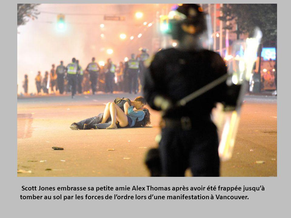 Scott Jones embrasse sa petite amie Alex Thomas après avoir été frappée jusqu'à tomber au sol par les forces de l'ordre lors d'une manifestation à Vancouver.